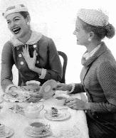 photo of two women having tea and laughing when one flips a plate over to see the back stamp