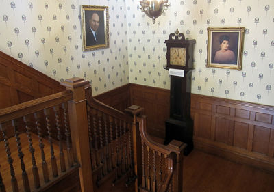 photo of 2nd floor landing with grandfather clock and portrait of Clavelli