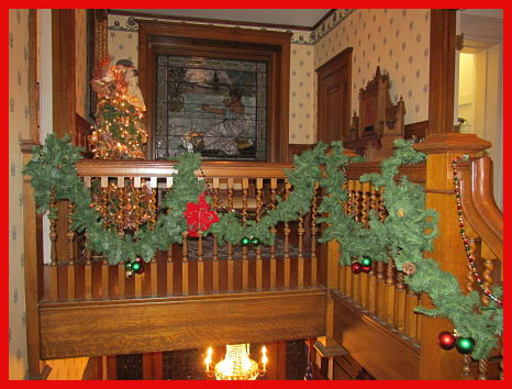 holiday decorations on upstairs staircase with stained glass window in background