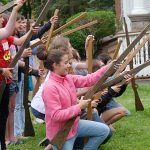 photo of kneeling students holding imitation wooden civil war rifles