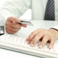 image of hand holding credit card with computer keyboard
