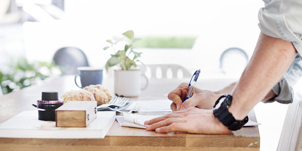 photo of man writing a document